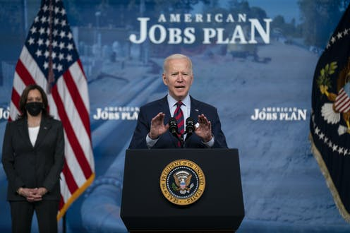"""President Biden giving a speech in front of a sign that says """"American Jobs Plan."""""""