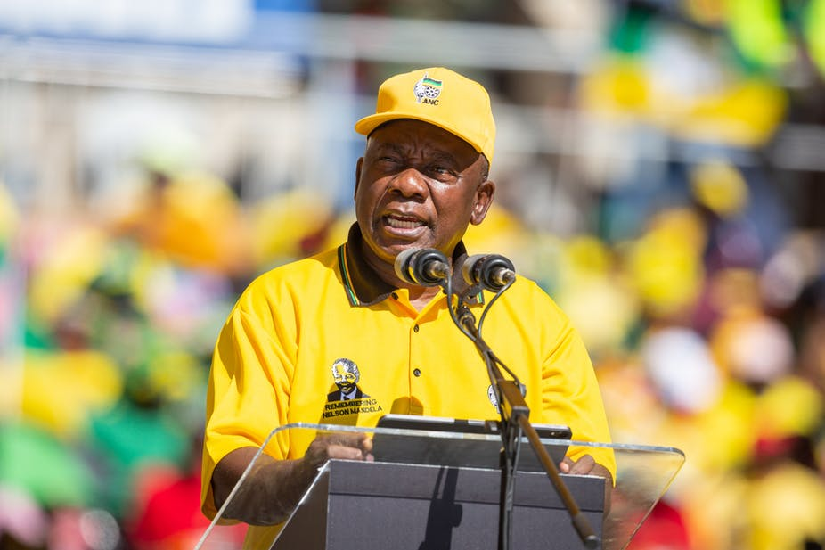 Black man in a yellow shirt and hat speaking at a podium