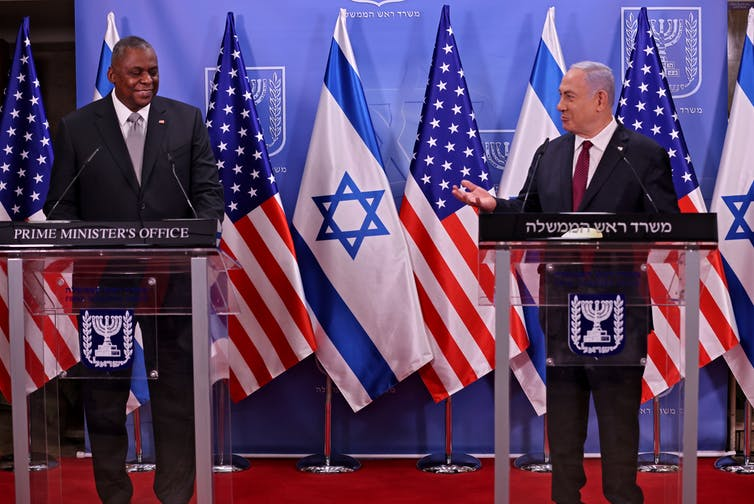 US defense secretary Lloyd Austin, left, and  Israeli prime minister Benjamin Netanyahu standing a lecterns on a stage in front of the US and Israeli flags.