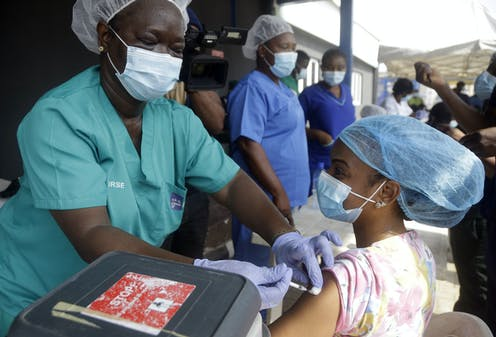 Hospital staff in scrubs and hair nets given vaccine doses to people.