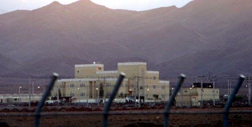 Large building behind security fence with mountains in background