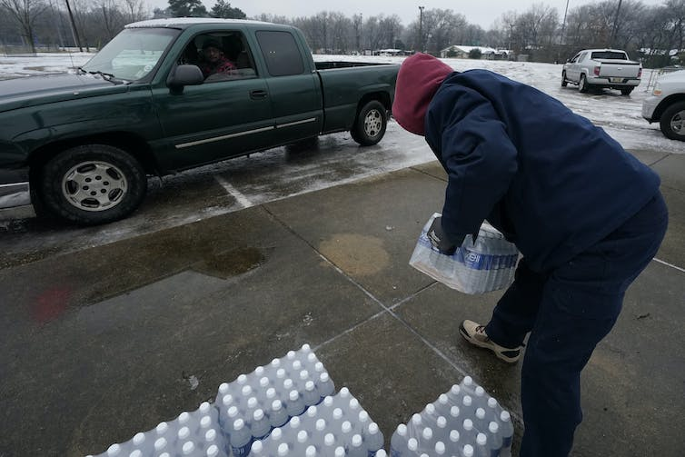 A city worker loads bottled water into a pickup truck.