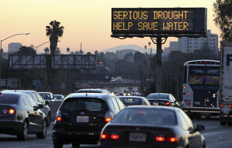 Cars drive on the Hollywood freeway during the morning commute as an electronic sign warns: 'Serious drought. Help save water.'