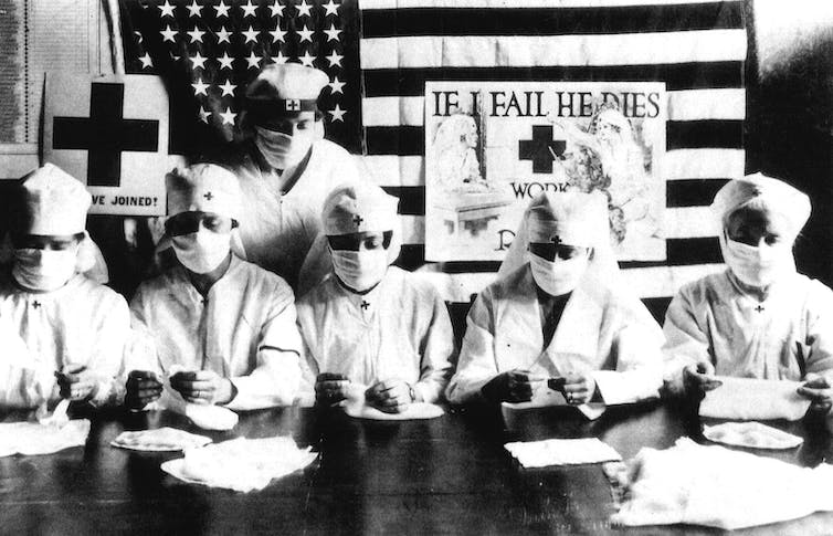 Red Cross volunteers from 1918 wearing masks.