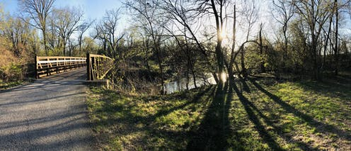 The sun shines through trees surrounding Ioway Creek in Ames, Iowa