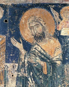 Christ with lifted arms, his head encircled by a halo, or nimbus, wearing a tunic and a mantle.