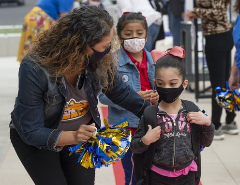 Students wearing masks get escorted to school by a teacher.