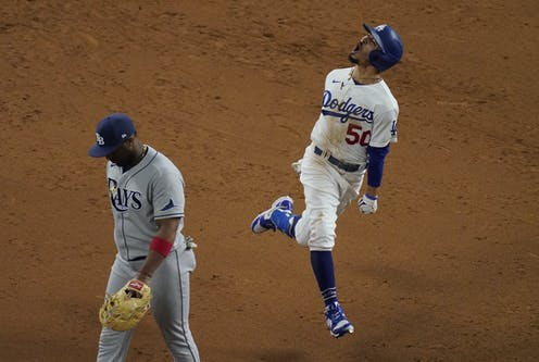 Los Angeles Dodgers player Mookie Betts shows jubilation after hitting a home run in the 2020 World Series while a member of the Tampa Bay Rays looks dejected while