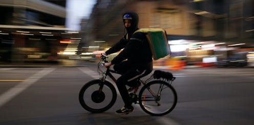 A food delivery rider on an electric bicycle.