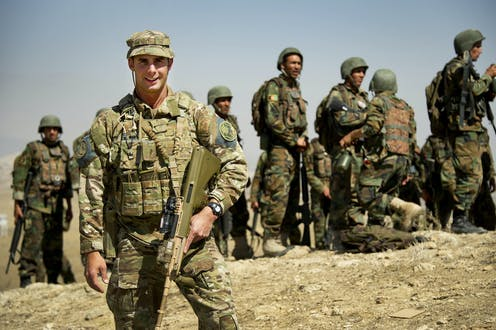 Australian Army soldier standing in front of Afghan officers