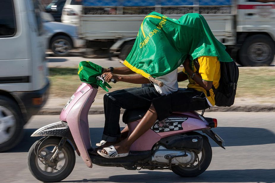 Supporters of ruling party Chama Cha Mapinduzi (CCM - Party of the Revolution) drive with the party's flag on their heads on a motorcycle.
