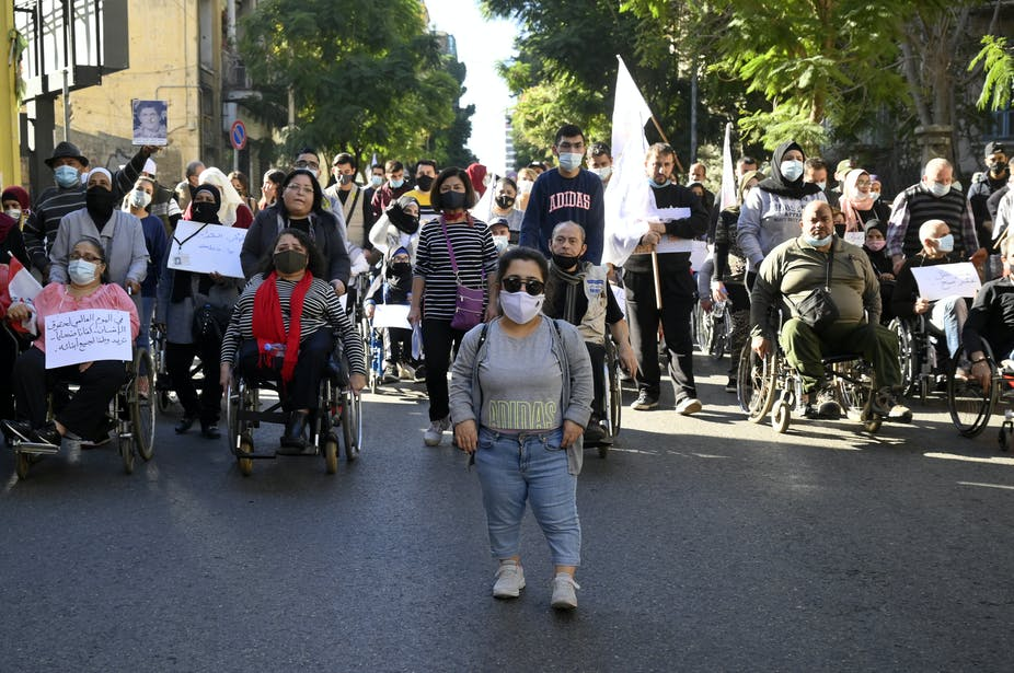 Group of disabled protesters with face masks and signs walking down a road in Beirut