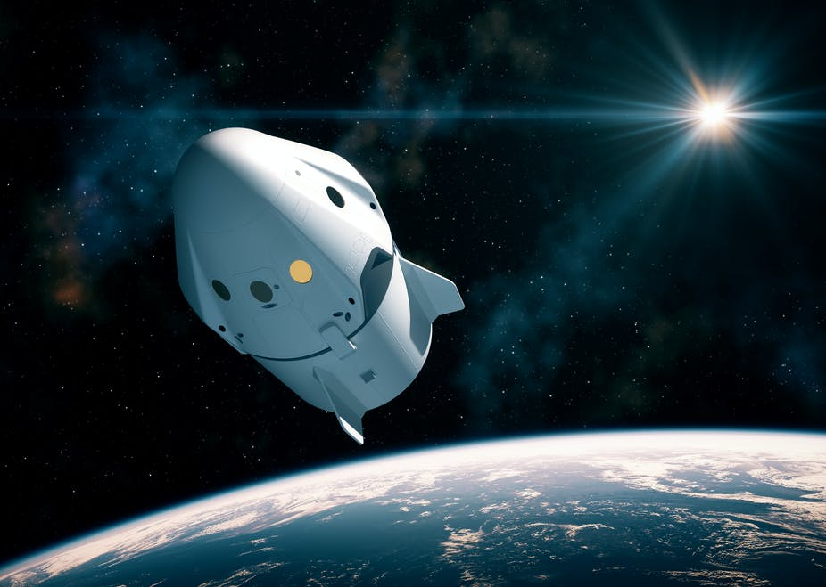 An artistic rendering of the Crew Dragon capsule floating through space above Earth.