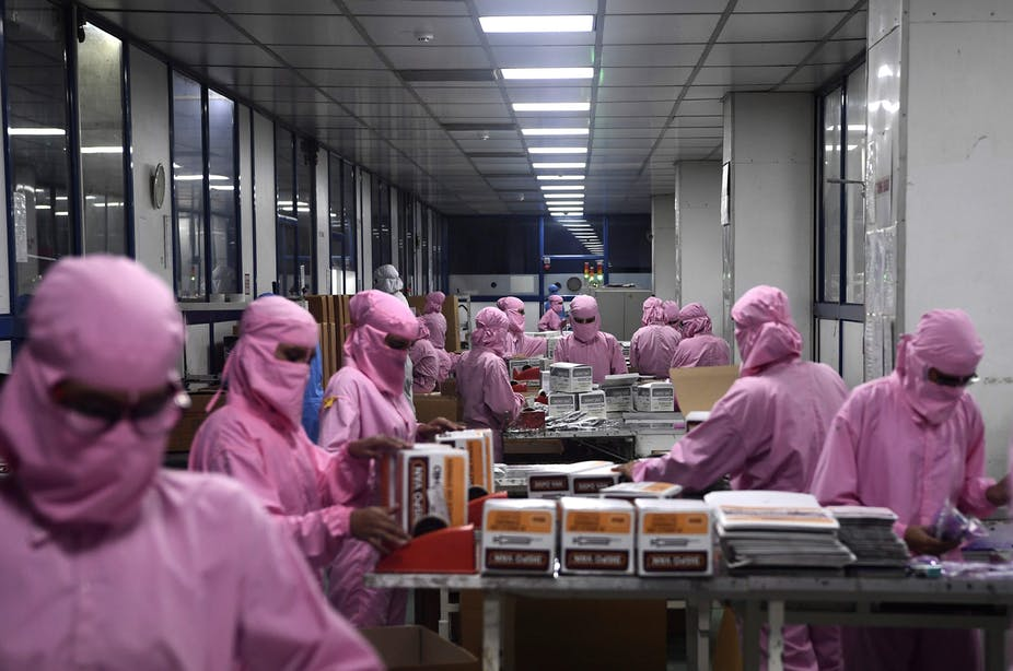 People wearing pink protective clothing and masks handle boxes on a table