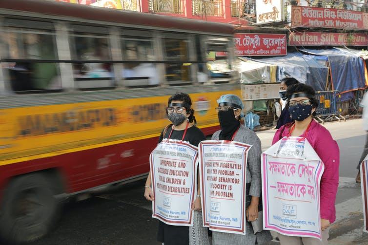 Three people wearing face masks and holding protest banners stand in street as bus drives past