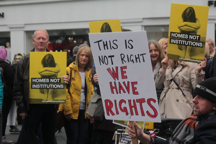 Disability rights protesters in Newcastle holding signs that say 'ths is not right we have rights' and 'homes not institutions'