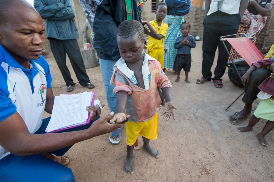 In Burkina Faso, a small boy is given a pill by a health worker as family look on.