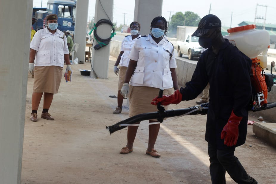 A man operates a chemical spray dispenser on a street, watched by women in uniform, all wearing protective masks and gloves