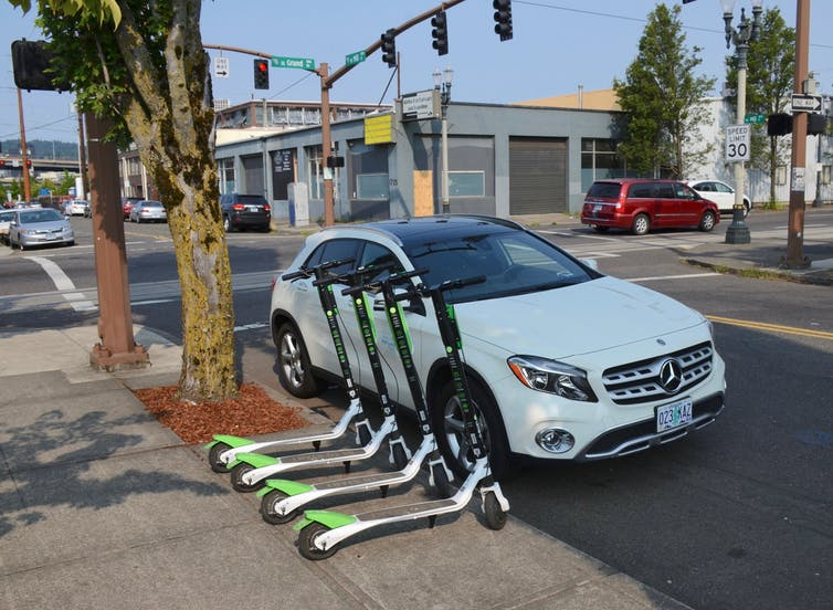 Four scooters lined up on the edge of a sidewalk, near the street and a car