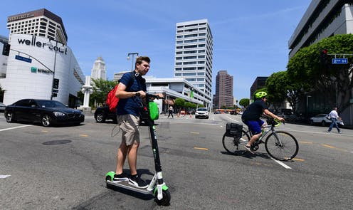 A car, e-scooter rider and cyclist share the road in Los Angeles