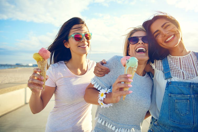 Laughing teenage girls eating ice cream cones as they walk along a beachfront