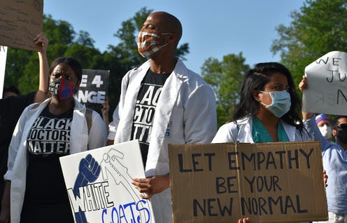 Health care workers wearing white coats protest racist health care.