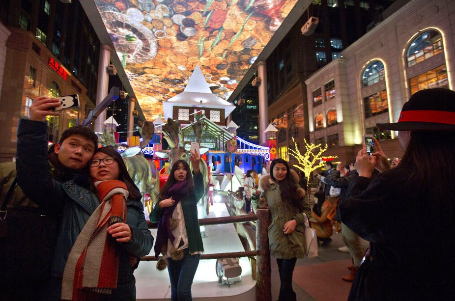 Shoppers pose for selfies near Christmas-themed decorations in a colorfully decoracted shopping mall in Beijing, China.