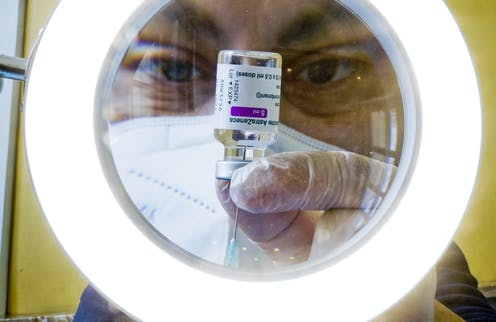 A man extracting AstraZeneca vaccine from a vial