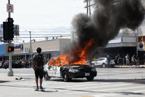 A skateboarder films a burning cop car in an intersection