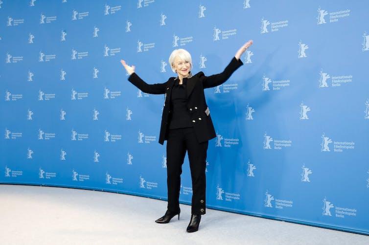 Helen Mirren dans un costume sombre avec des boutons dorés et des bottes à talons aiguilles