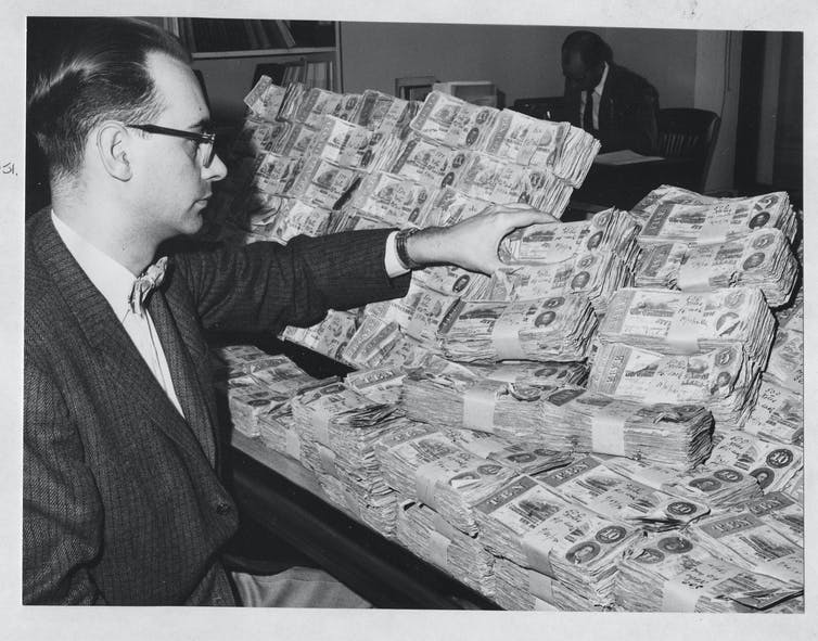 A man in glasses looks at stacks of Confederate currency