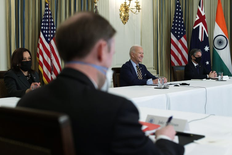 Vice President Kamala Harris, President Joe Biden and Secretary of State Anthony Blinken at meeting tables with flags