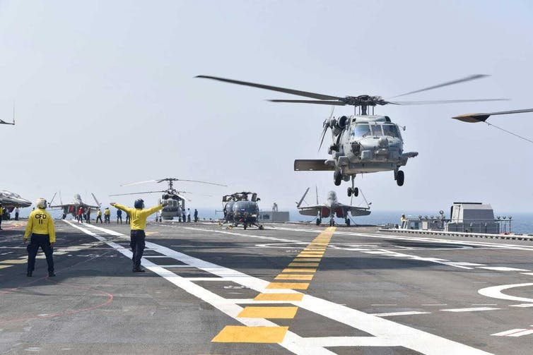 Helicopters landing on an aircraft carrier
