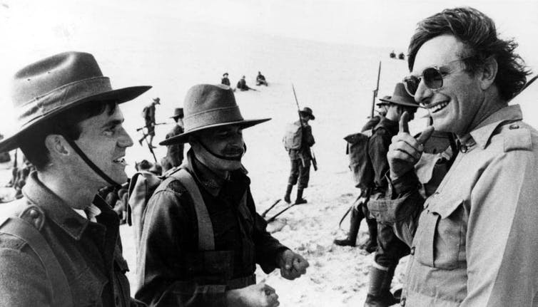 black and white photo of men on war film set