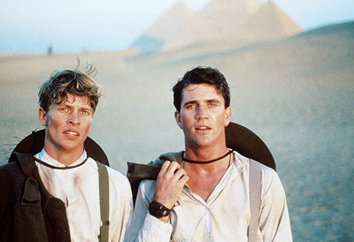 Two young men stand in front of pyramids