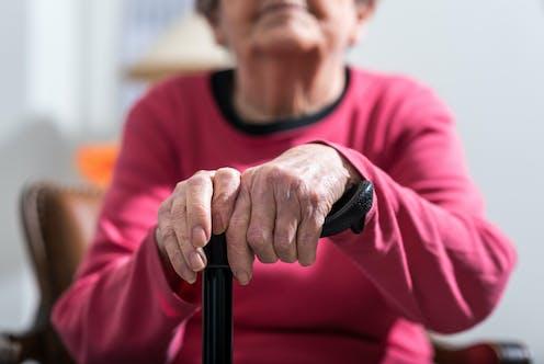 An elderly woman's hands rest on a walking stick.