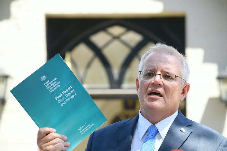Prime Minister Scott Morrison holds up a copy of the aged care royal commission's final report.