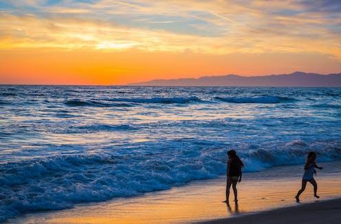 Anak-anak berdiri di pinggir pantai saat matahari tenggelam.