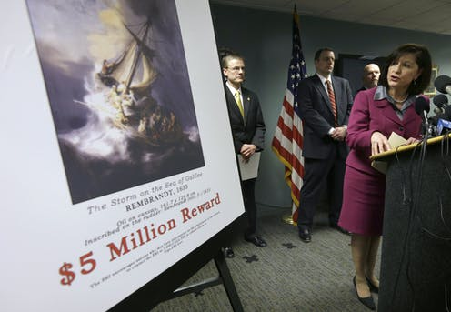 FBI agents with reward poster for missing art.