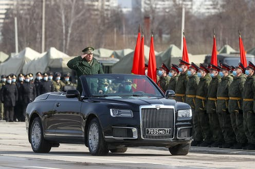 A Russian general in a convertible limousine salutes Russian troops as he drives past.