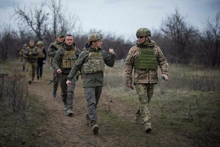 Ukraine's president Volodymyr Zelensky and military aides dressed in uniform in Ukraine's eastern conflict zone.