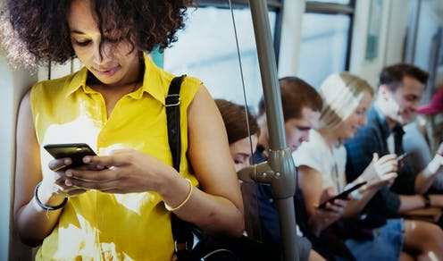 Five people in a train carriage all looking at their phones.