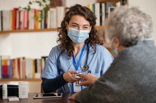 A doctor checks an elderly ladies blood-oxygen levels.