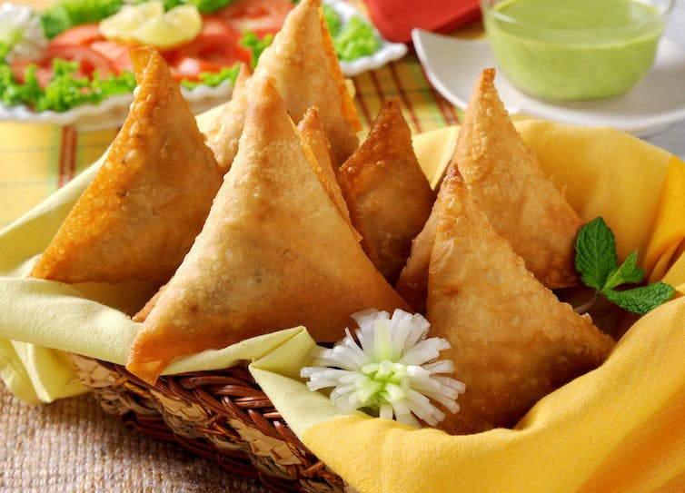 A basket of fried samosas.