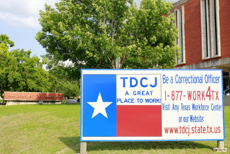 Photo of the TDCJ headquarters with a sign outside painted like the flag of Texas