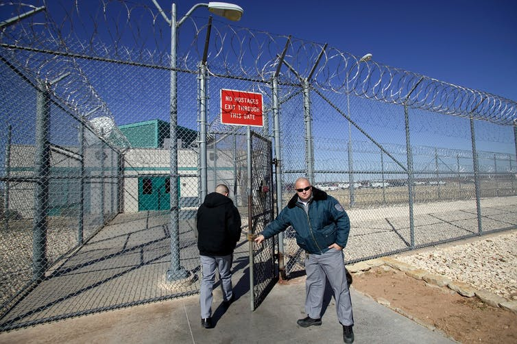 Guard opens the gate for a person in a high chain link fence topped with barbed wire