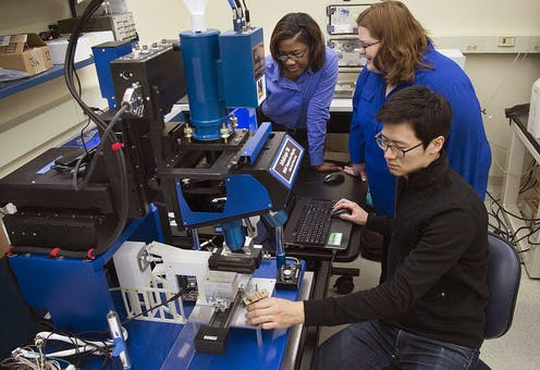 Researchers working in a lab studying effect of heat on hair with infrared microscope.