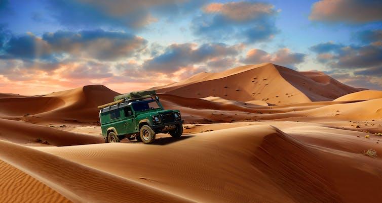 A green land rover on desert dunes