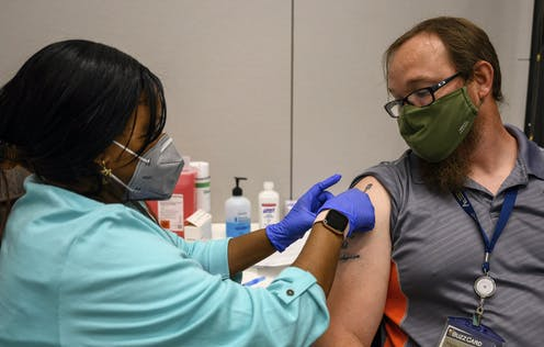 A female nurse wearing blue gloves gives a bespectacled man a Pfizer COVID-19 shot on the campus of Georgia Tech