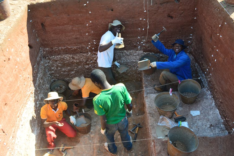 people excavate stone tools below the ground's surface